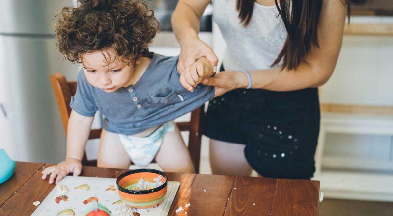 Bebis klättrar upp på ett bord och person håller i armen