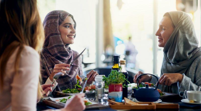 Två personer äter sallad och tittar på varandra vid ett bord